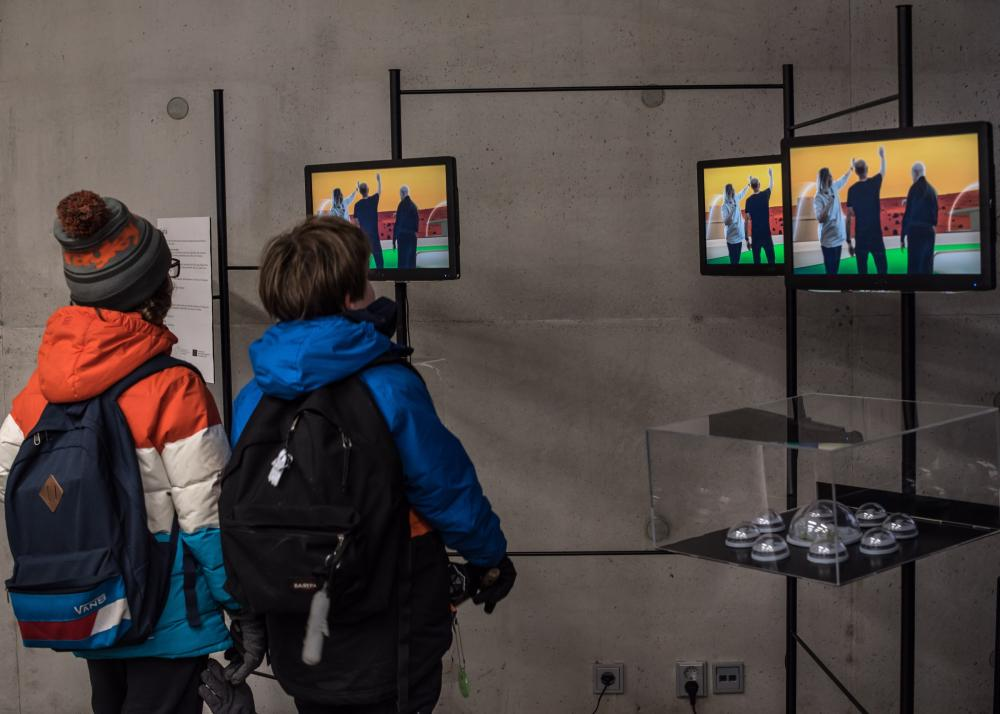 Two boys looking at the screens in the exhibition of Recovered Utopias