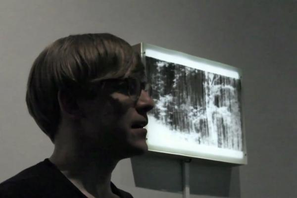 Tuomo Rainio with artwork in the background