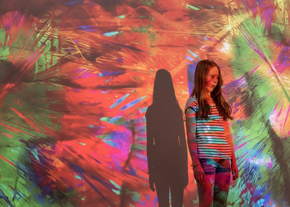 One girl standing alone, colors projected on the wall and her body.